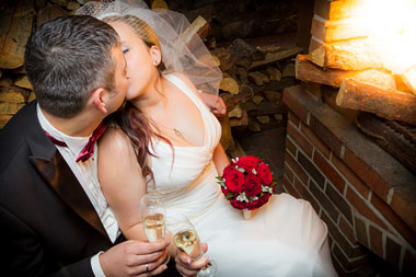 newly weds toasting in front of fireplace
